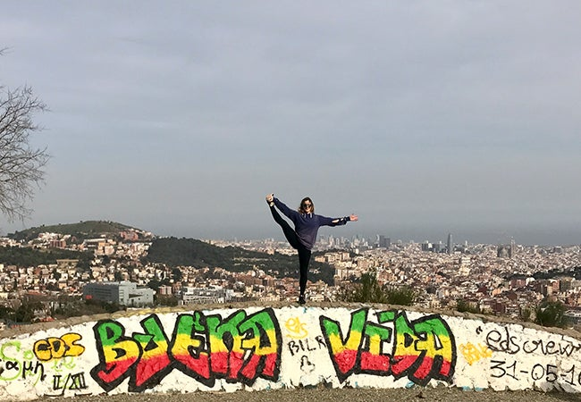 MBA student Elizabeth Cooke balances on one foot while standing in front of a scenic view of Barcelona.