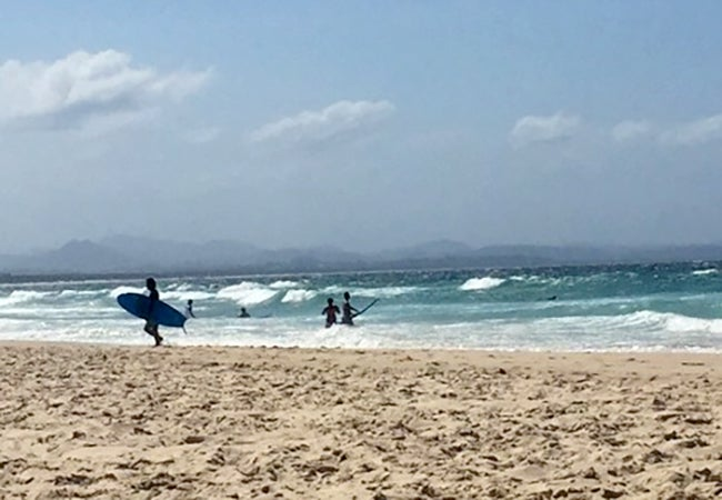 Surfers carry their boards out to the beach as waves crest nearby on a sunny day in Australia.