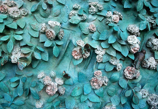 A smattering of teal-colored leaves dotted with white and pink flowers on the door at La Sagrada Familia.