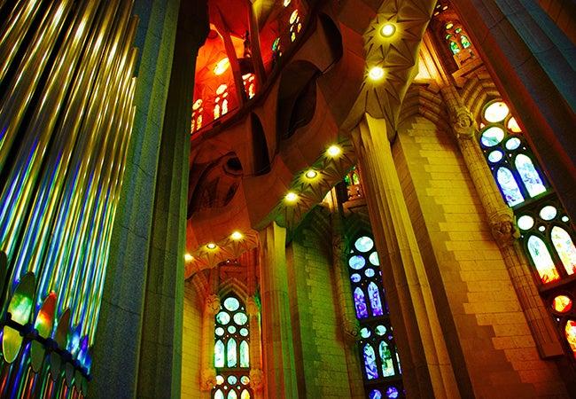 A rainbow of colors emanate from stained glass windows inside La Sagrada Familia Basilica.