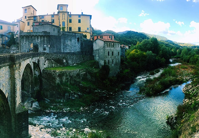 Water flows under a stone bridge on a bright, sunny day in the city of Pisa.