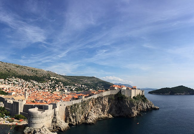 An aerial view shows a stone wall surrounding the city of Dubrovnik, perched on a cliff by the sea.