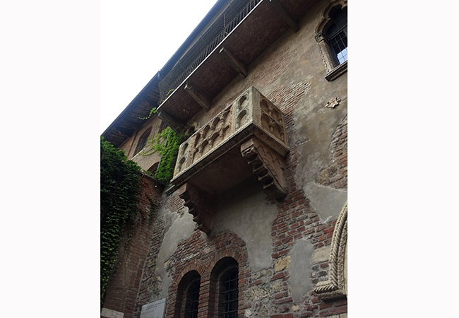 A stone balcony juts out from a faded brick wall in Verona.