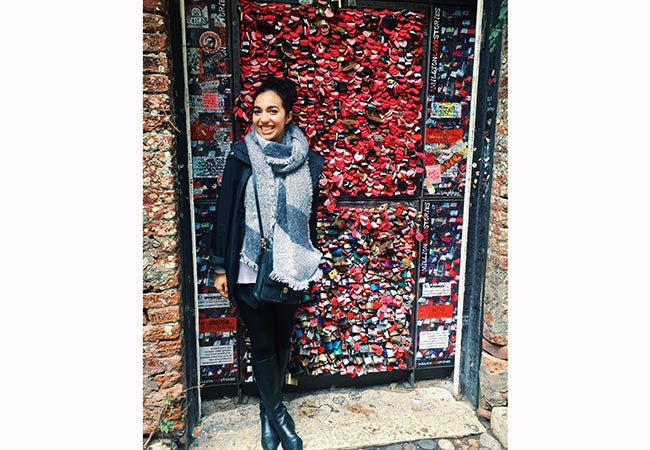 Undergraduate business student Alexandra Grieco stands in front of a wall festooned with red and pink objects.
