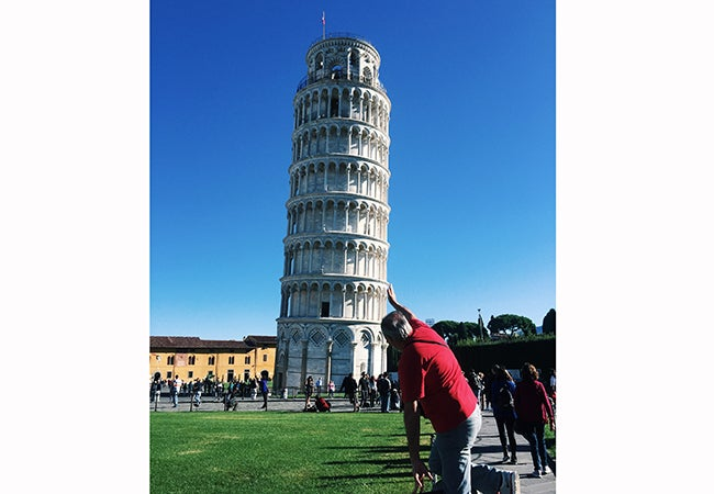 A man in a red shirt holds up a hand as if to correct the posture of the Leaning Tower of Pisa.