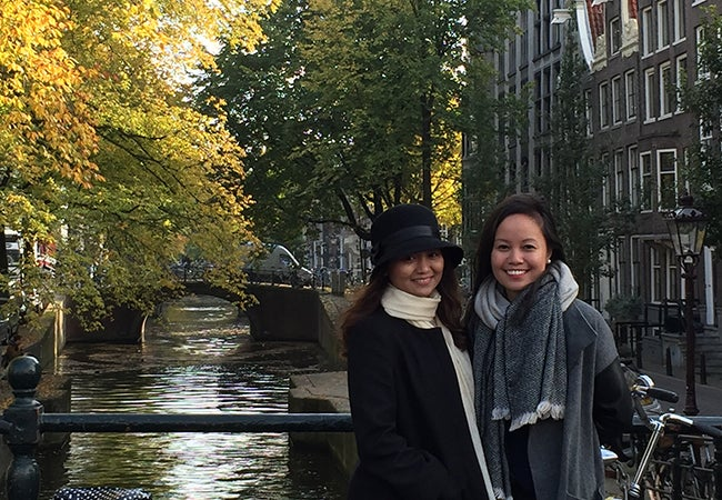 MBA student Kimberly Rodriguez stands with a friend on a bridge next to a canal in the fall.