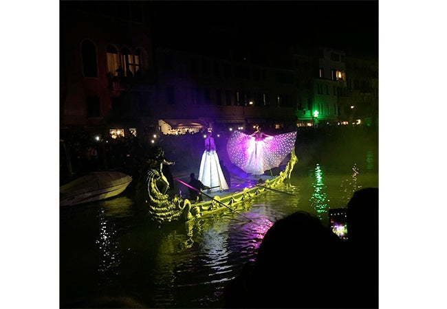 Two figures in capes and dresses appear to float atop a gondola, surrounded by a purple glow, during Carnival in Venice.