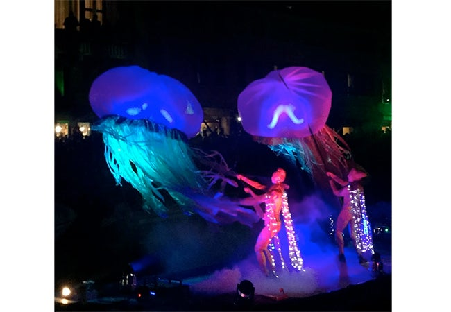 Two figures shake large objects that resemble jellyfish, illuminated in blue and green light, during Carnival in Venice, Italy.