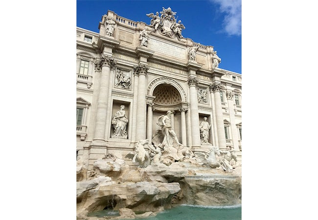 Stone figures are etched into the stone surrounding Trevi Fountain in Rome, Italy.
