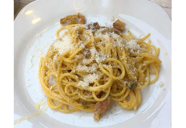 A close-up of a dish of carbonara pasta sprinkled with cheese and served in Rome, Italy.