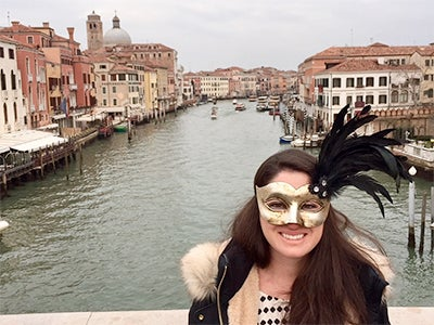 MBA student Ashley Grand wears a shiny gold mask while standing in front of a waterway lined with buildings in Italy.