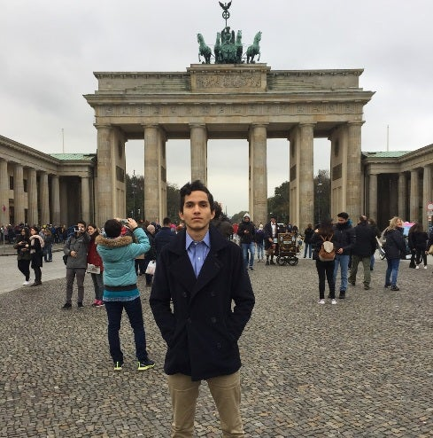 Undergraduate business student Aldo Gonzalez stands in front of Brandenburg Gate in Berlin while studying abroad.