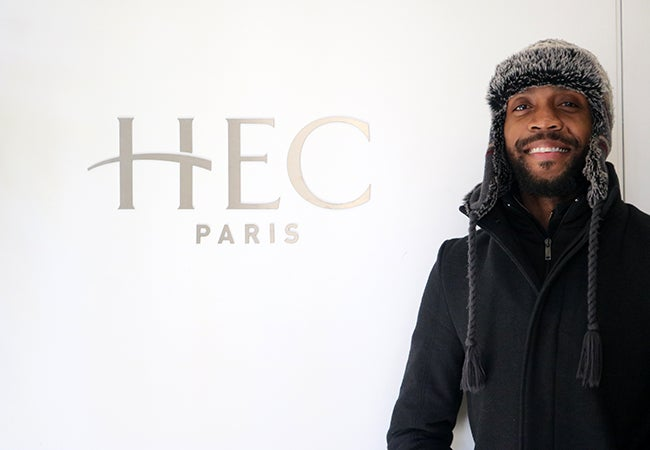 """MBA student Calvin Mack wears a warm hat and stands in front of a sign that says """"HEC Paris."""""""