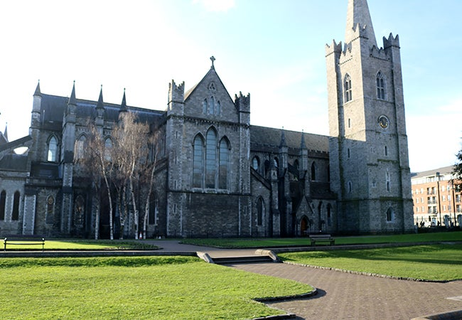 A grand stone building on the grassy campus of Trinity College in Ireland.