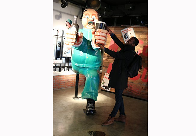 MBA student Calvin Mack acts as if he is taking a beer away from a large cartoonish character installed at Guinness Storehouse.