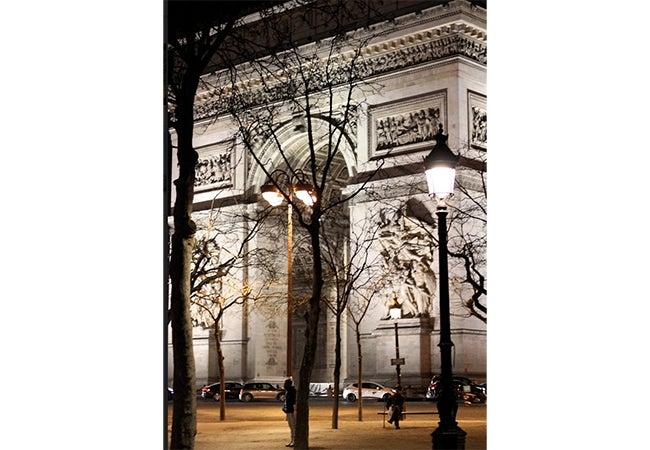Cars circle the Arc de Triomphe at night in Paris.