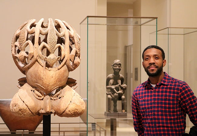 MBA student Calvin Mack stands in front of ancient artifacts on display at the Louvre.