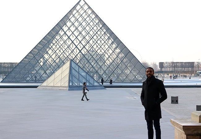 MBA student Calvin Mack stands outside and in front of the Louvre's iconic glass triangle ceiling.