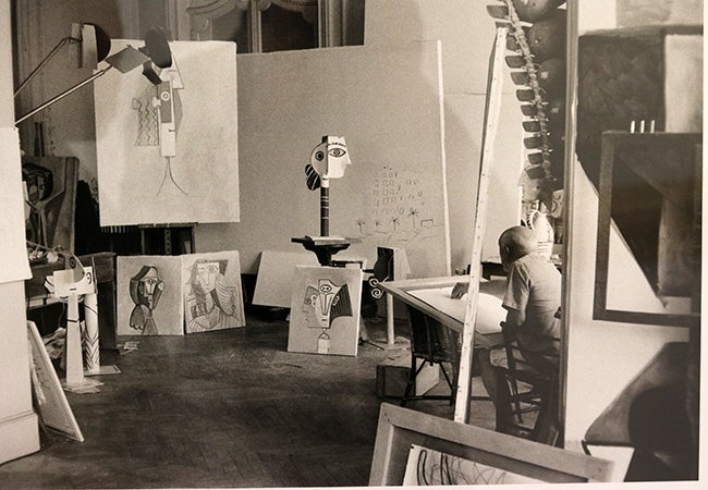 A black-and-white photo shows Picasso hunched over a painting in his studio while surrounded by works in progress.