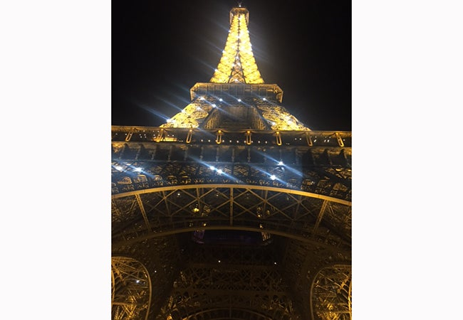 A view of the illuminated Eiffel Tower at night, if looking up from below.