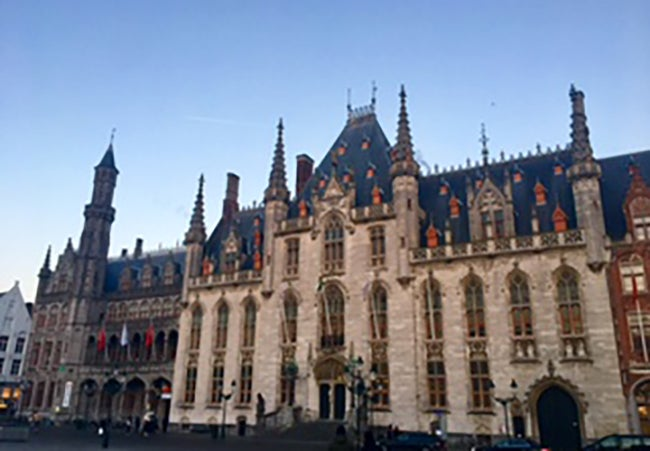 A stone building in Bruges, Belgium with many narrow turrets on a clear day.