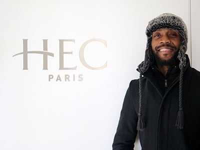 "MBA student Calvin Mack wears a warm hat and stands in front of a sign that says ""HEC Paris."""