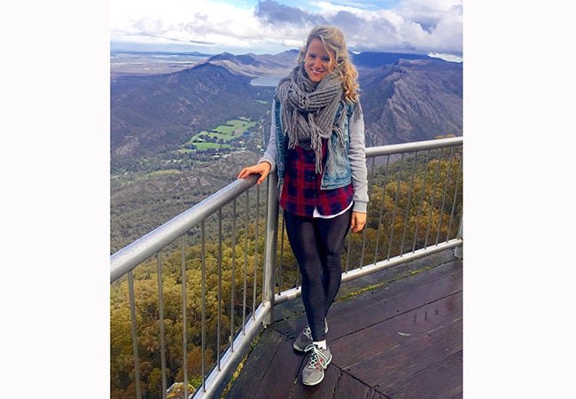 MBA student Cara Witt-Landefeld rests one hand on a fence while taking in the beautiful mountain views in Australia.