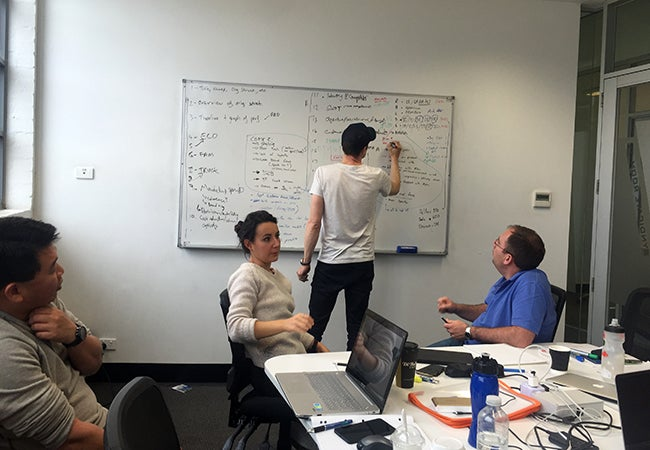 One student writes on a whiteboard while three others discuss their strategy during a group work session at Melbourne Business School.