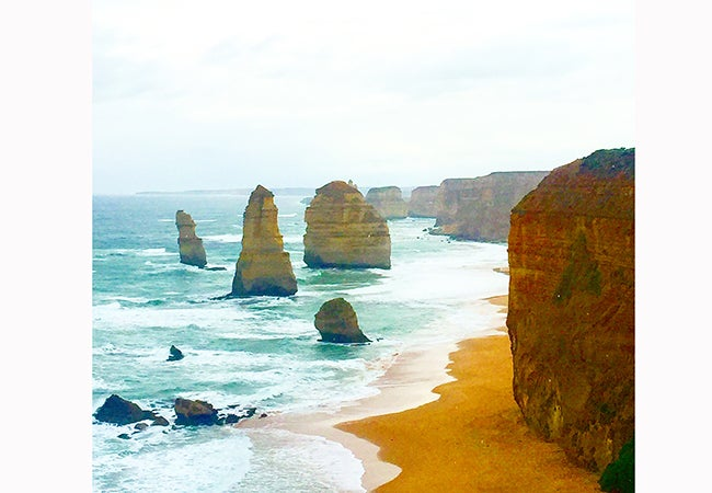 Gentle waves from the sea swish around orange cliffs and rock formations in Australia.