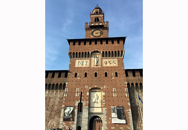 A beautiful clock ticks away time on the brown decorative facade of Castello Sforzesco.