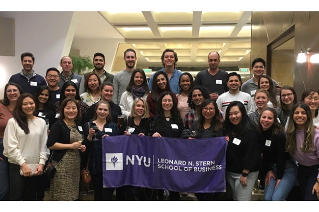 """Students holding a banner with """"NYU Leonard N. Stern School of Business"""""""