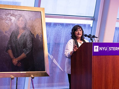Dean Menon speaks at podium with portrait of her displayed on her right