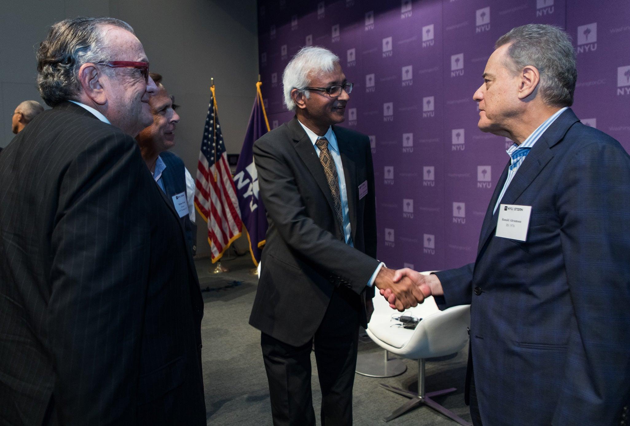 Photo of Dean Raghu Sundaram shaking hands with an alumnus