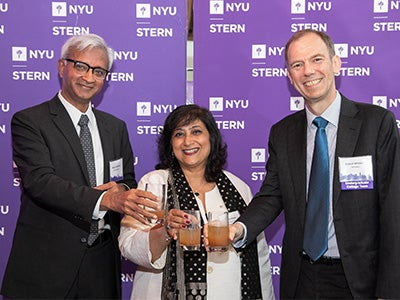 Dean Sundaram, Dean Menon, and Vice Dean Whitelaw smile and clink glasses