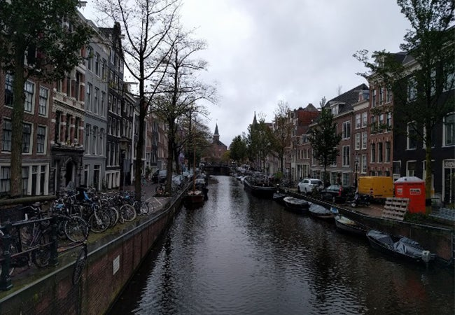 A quiet canal in Amsterdam lined with trees, buildings, and brick streets.