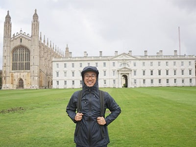 Stern MBA student Dennis Au, wearing rain gear, stands in front of a building on the campus of the London Business School.