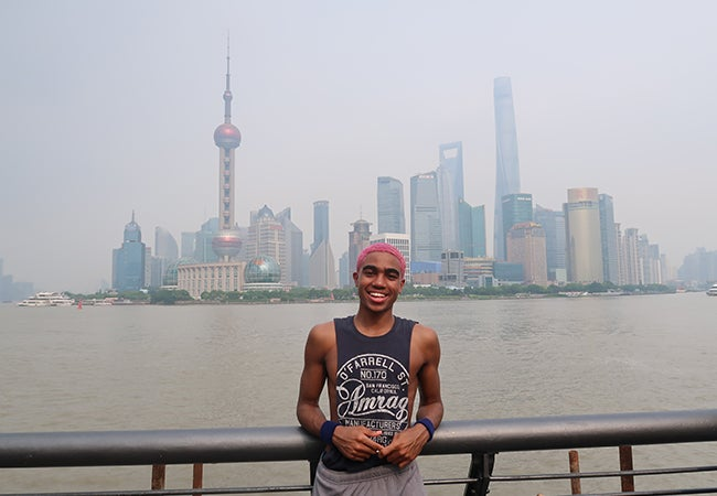 Undergraduate business student Dimitri Pun stands in front of a river with the Shanghai skyline in the background.