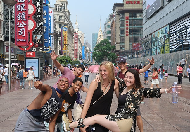 Business student Dimitri Pun poses with friends on a busy street while studying abroad in Shanghai.