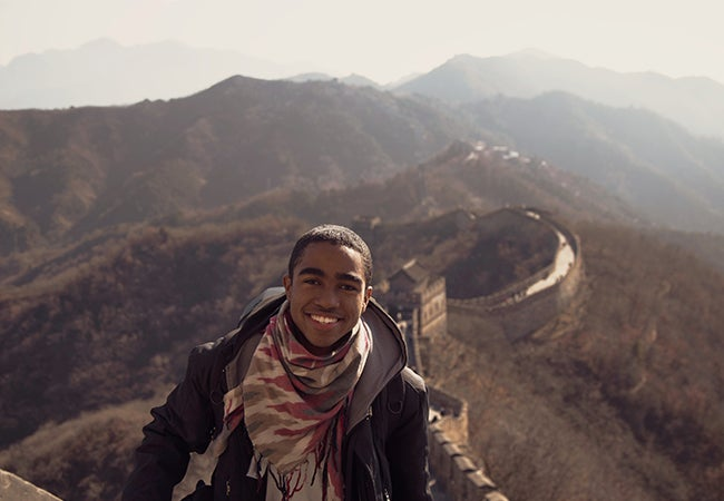 Business student Dimitri Pun smiles at the camera while walking the Great Wall of China.