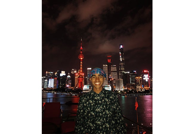 Undergraduate business student Dimitri Pun stands in front of a Shanghai city scene at night.