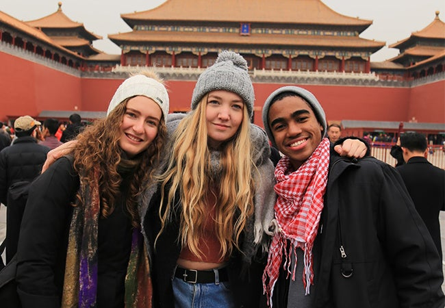 Undergraduate business student Dimitri Pun links arms with friends in front of a red building while studying abroad in Shanghai.
