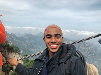 Dimitri Pun holds onto a rope fence while smiling in front of a high-elevation mountainous scene.