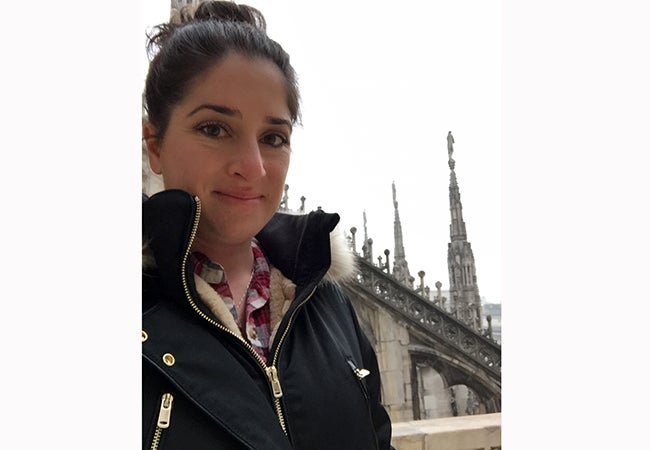 MBA student Ashley Grand, dressed in cold-weather gear, stands before beautiful stonework at the Duomo in Milan.