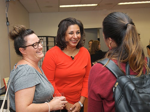 Stern faculty and students chat at an Alumni event