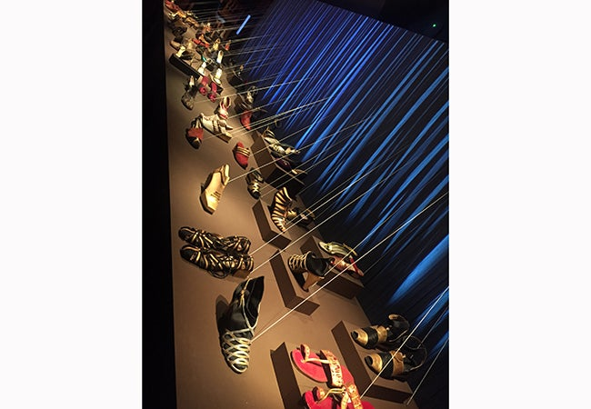 Pairs of colorful sandles, strappy heels, and flats are shown on display at a museum exhibit.