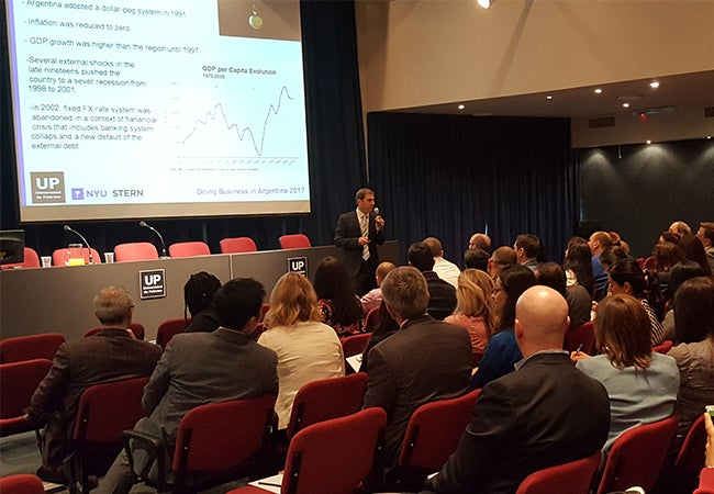 A presenter speaks to executive MBA students about Argentina's economy during their visit to Buenos Aires.