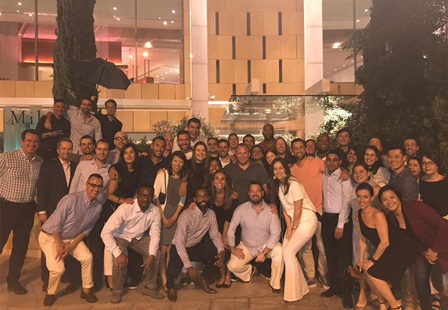 A group of Executive MBA students gather outside for a photo together in Greece. One holds an umbrella.
