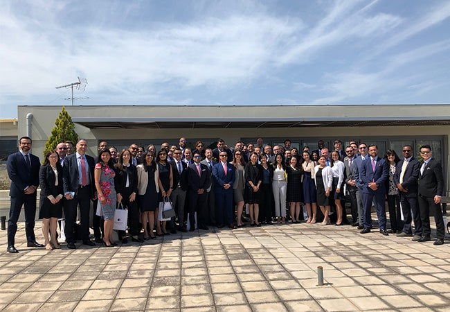 A large group of Executive MBA students pause outside for a photo together in Greece.