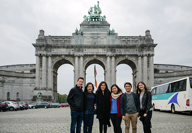 A group of students stand together before a large stone gate with huge archways and sculptures on top..