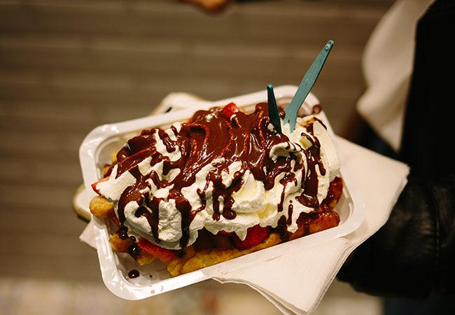 Someone holds out a container with a Belgian waffle topped with generous helpings of fruit and whipped cream and drizzled with chocolate.